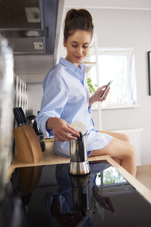 Young woman preparing coffee in the morning, using smartphone - ABIF00908