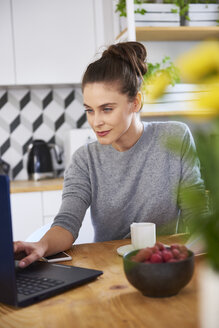 Young woman working from home, using laptop - ABIF00914