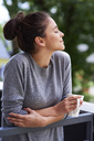 Young woman drinking morning coffee on the balcony - ABIF00920