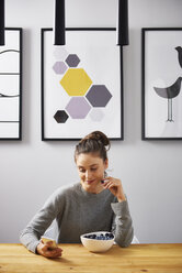 Young woman sittin at home, eating berries, reading text messages - ABIF00926