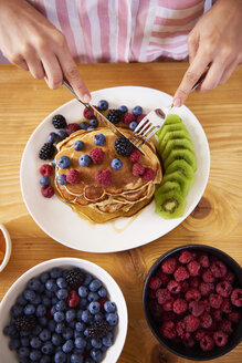 Woman eating pancakes with berries for breakfast - ABIF00932
