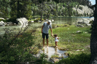 Spain, Father and daughter exploring mountain lake, standing ankle deep in water - GEMF02340