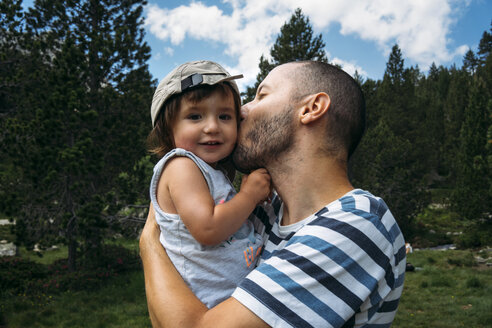 Spain, Father hugging and kissing his little daughter in nature - GEMF02343