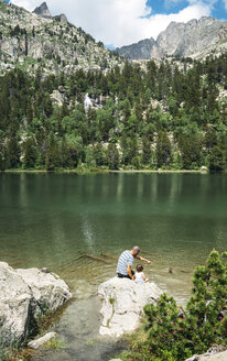 Spain, Father and daughter sitting on a rock at a mountain lake, feeding ducks - GEMF02349