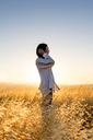 Woman standing in a field of golden grass in sun drenched hills of California. - AURF01655
