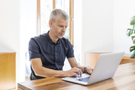 Mature man using laptop on wooden table - TCF05687