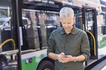 Mature man using cell phone in the city at a bus - TCF05696