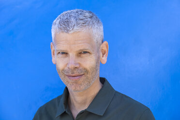 Portrait of a smiling mature man at blue wall - TCF05702