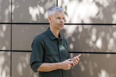 Portrait of a mature man with cell phone at a wall looking sideways - TCF05705