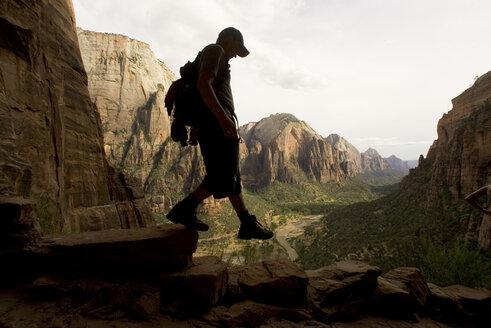 A teenage boy walks down a shady cliff. - AURF01830