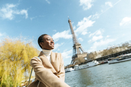 France, Paris, Smiling woman at river Seine with the Eiffel Tower in the background - KIJF02001