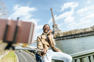 France, Paris, Woman sitting on bridge over the river Seine with the Eiffel tower in the background taking a selfie - KIJF02004