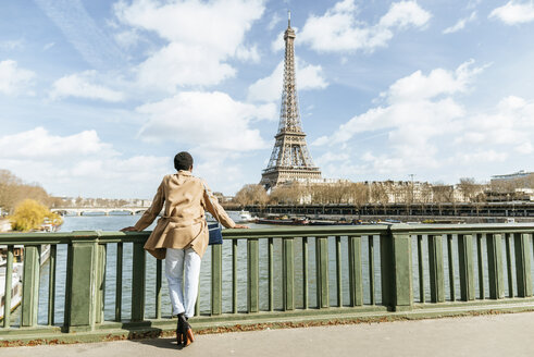 France, Paris, Female tourist looking towards the Eiffel tower and the Seine river - KIJF02007