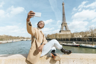 France, Paris, Woman sitting on bridge over the river Seine with the Eiffel tower in the background taking a selfie - KIJF02010