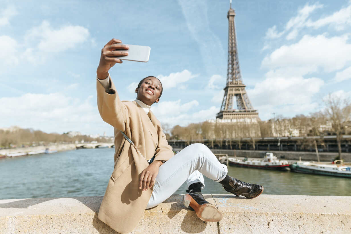 France, Paris, Woman sitting on bridge over the river Seine with the Eiffel tower in the background taking a selfie - KIJF02010 - Kiko Jimenez/Westend61