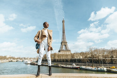 France, Paris, Smiling woman standing on a bridge with the Eiffel tower in the background - KIJF02013