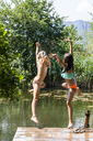 Two carefree girls jumping into pond - TCF05721