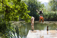 Two carefree girls jumping into pond - TCF05724