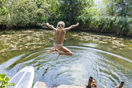 Carefree girl jumping into pond - TCF05730