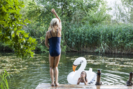 Two girls at a pond with inflatable pool toy in swan shape - TCF05736