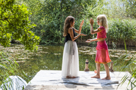 Two girls standing on jetty at a pond in fancy dresses doing a hand clapping game - TCF05742