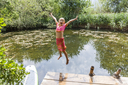 Carefree girl jumping into pond - TCF05745