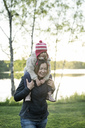 Finland, Kuopio, mother carrying daughter piggyback at a lake - PSIF00028