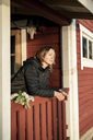 Finland, Kuopio, woman on the veranda of a cottage in the countryside - PSIF00031