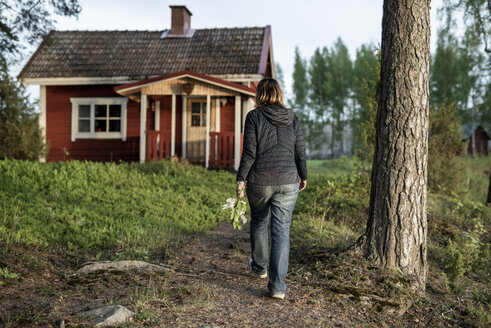 Finland, Kuopio, woman walking at a cottage in the countryside - PSIF00034