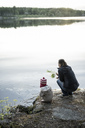 Finland, Kuopio, mother and daughter crouching at a lake - PSIF00037