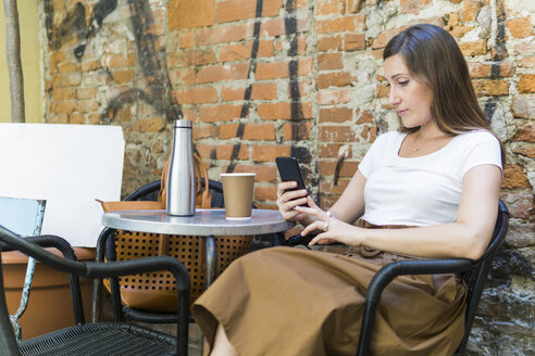 Woman using cell phone at an outdoor cafe - FBAF00002