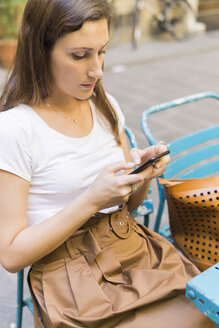 Woman sitting outdoors on a chair using cell phone - FBAF00011