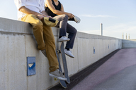 Close-up of two young men with skateboards sitting on a wall - AFVF01481