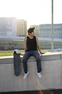 Young man sitting on urban wall next to skateboard at sunset - AFVF01484