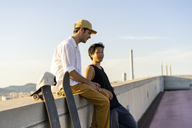 Two young men resting next to skateboards at a wall - AFVF01490