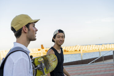 Two young men with skateboard on the move talking - AFVF01493