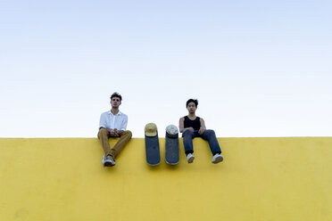 Two young men with skateboards sitting on a high yellow wall - AFVF01496