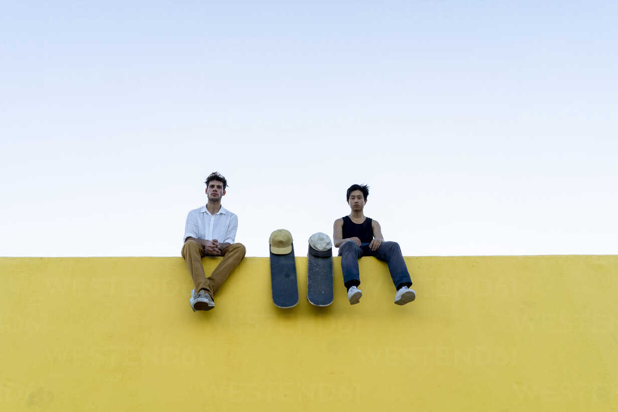 Two young men with skateboards sitting on a high yellow wall - AFVF01496 - VITTA GALLERY/Westend61