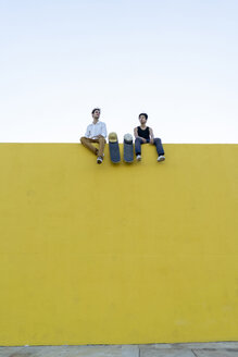 Two young men with skateboards sitting on a high yellow wall - AFVF01499