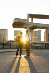 Portrait of two young men with skateboards in the city at sunset - AFVF01502