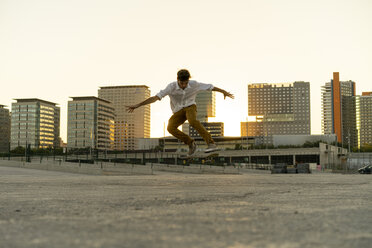 Young man doing a skateboard trick in the city at sunset - AFVF01505