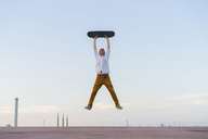 Young man jumping in the air holding a skateboard - AFVF01508