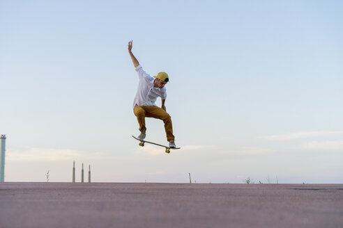 Young man doing a skateboard trick on a lane at dusk - AFVF01511