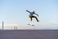 Young man doing a skateboard trick on a lane at dusk - AFVF01514