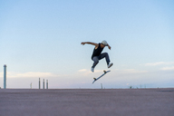 Young man doing a skateboard trick on a lane at dusk - AFVF01517