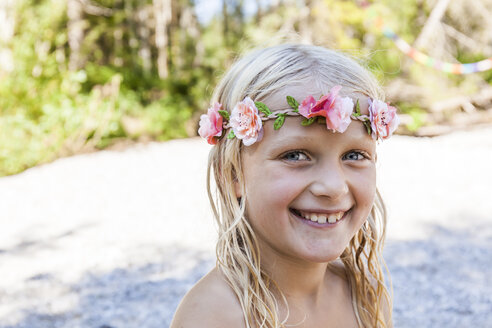 Portrait of happy girl wearing flower crown outdoors in summer - TCF05754