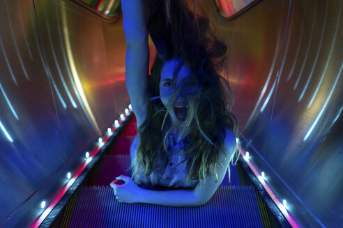 Portrait of blue illuminated screaming young woman on steps of lighted escalator - AFVF01528