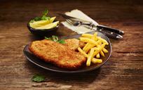 Pork escalope and French Fries on plate, lemon in bowl - KSWF01973