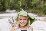 Portrait of happy girl at the riverside wearing leaves on her head - TCF05768
