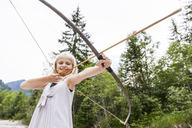 Smiling girl aiming with bow and arrow in the nature - TCF05786